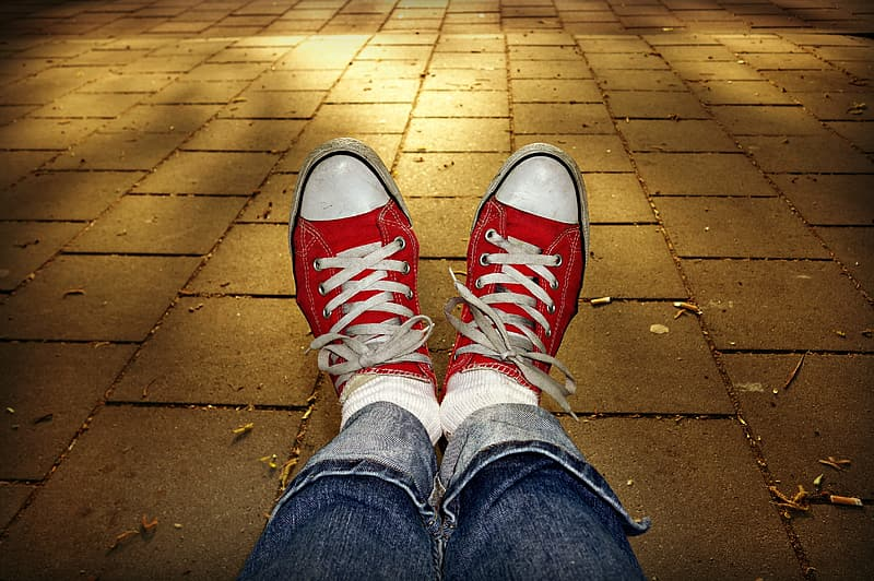 Person in blue denim jeans and red and white converse all star high top sneakers