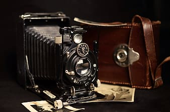 Black folding camera with brown leather bag