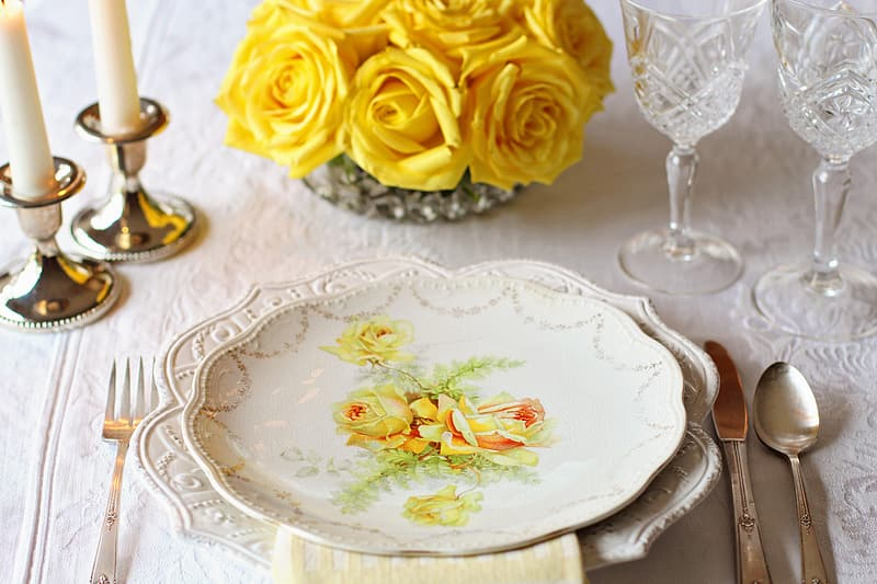 White and yellow floral ceramic plate near butter knife and spoon table setting