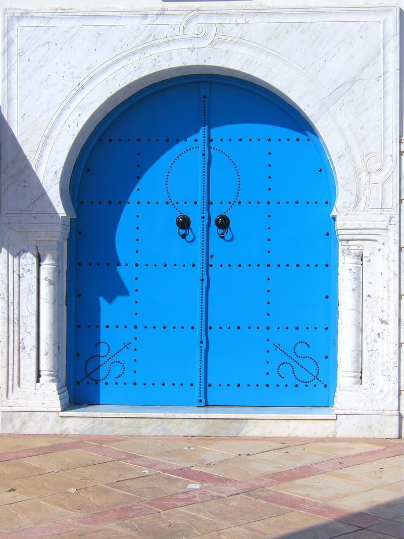 Blue metal door on white concrete wall