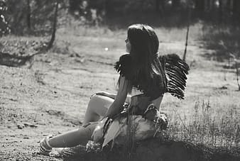 Gray scale photo of a woman with black wings and white skirt sitting on ground