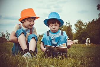 Two boys reading book while sitting on green grass field