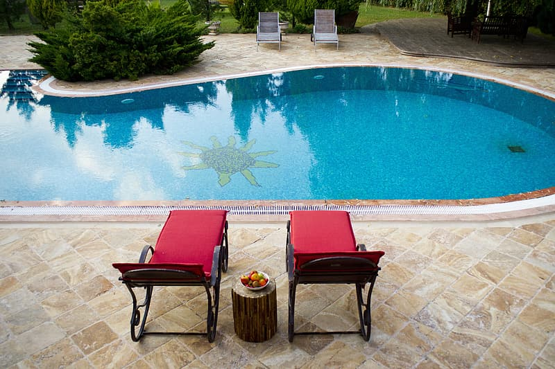 Two red-and-black outdoor loungers beside outdoor pools