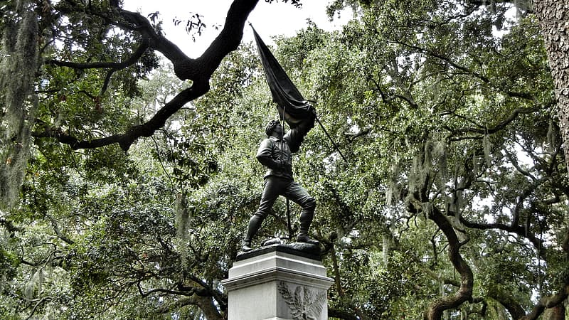 Man holding flag statue under green trees