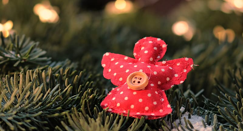 Angel-shaped red and white polka-dot ornament on green surface