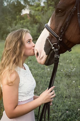 Woman in white tank top holding brown horse saddle