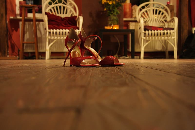 Red and brown leather peep toe heeled sandals on brown wooden table