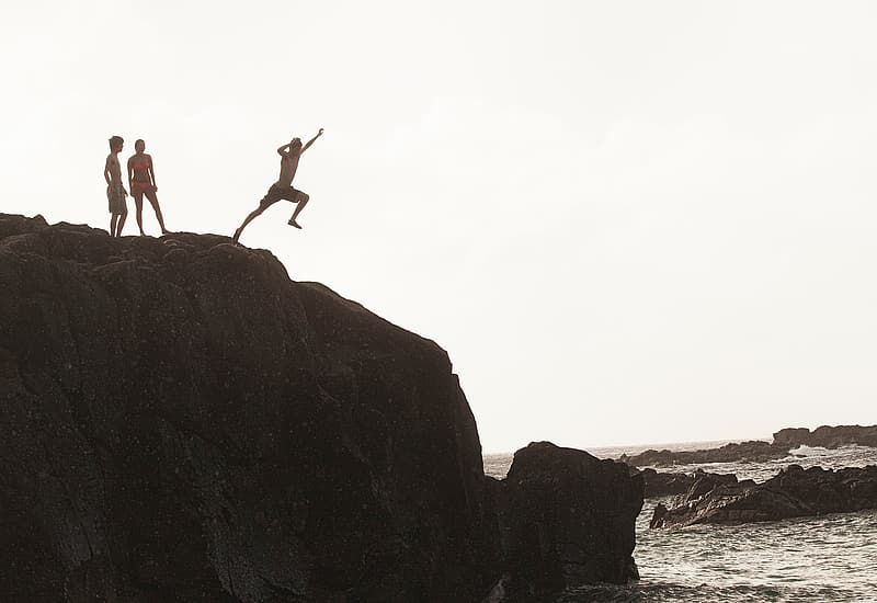 Man jumping on brown rock formation during daytime