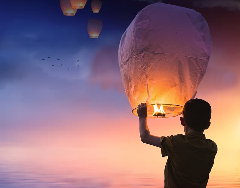 Person holding floating lantern under sunset