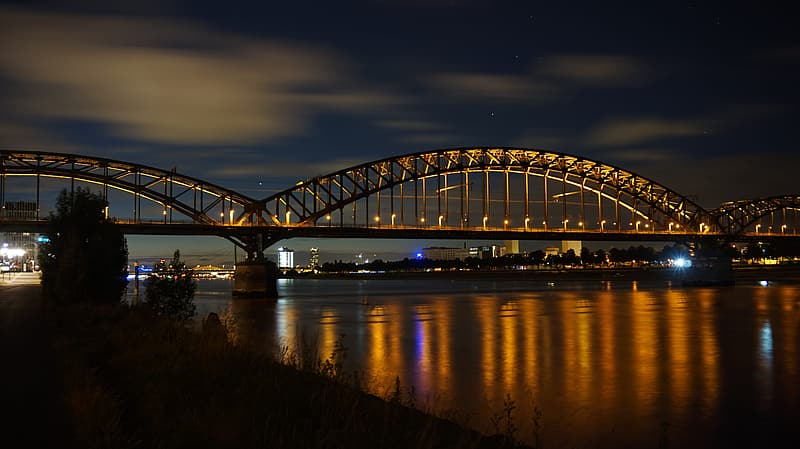 Gray metal bridge over river during night time