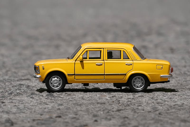 Shallow focus photography of yellow taxi cab die-cast model