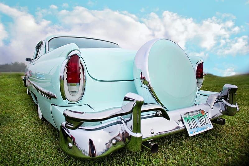 Photo of vintage teal car parked on green grass field