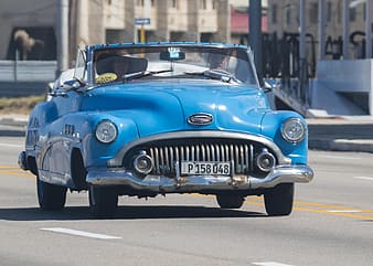 Blue classic car on road during daytime