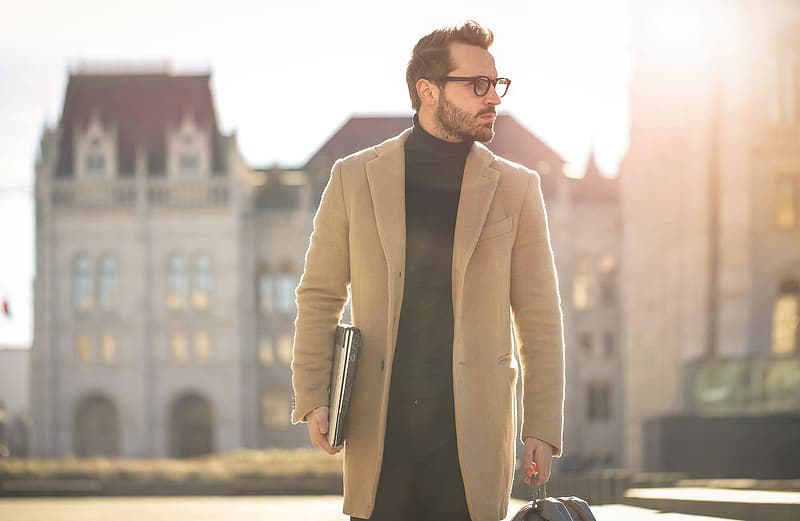 Young white bearded male wearing black turtleneck top with long overcoat and eyeglasses carrying a laptop,as he walks on the street