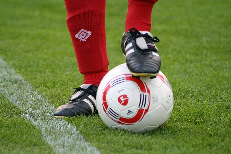 Person in red pants and black and white nike soccer cleats standing on green grass field