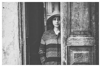 Grayscale photo of a woman standing near door