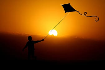 Silhouette of child playing kite