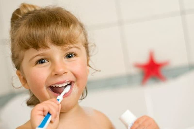 Toddler girl brushing her teeth and holding toothpaste soft-tub