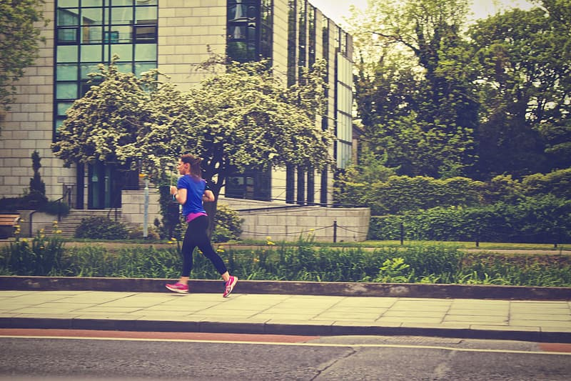 Woman running along the street near building during daytime