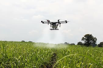 Black drone flying over green grass field during daytime