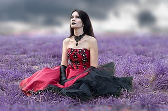 Woman wearing red and black strapless dress sits on purple grass field at daytime
