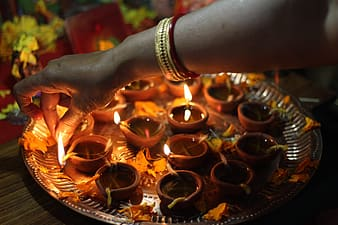 Person holding lighted candles on brown tray