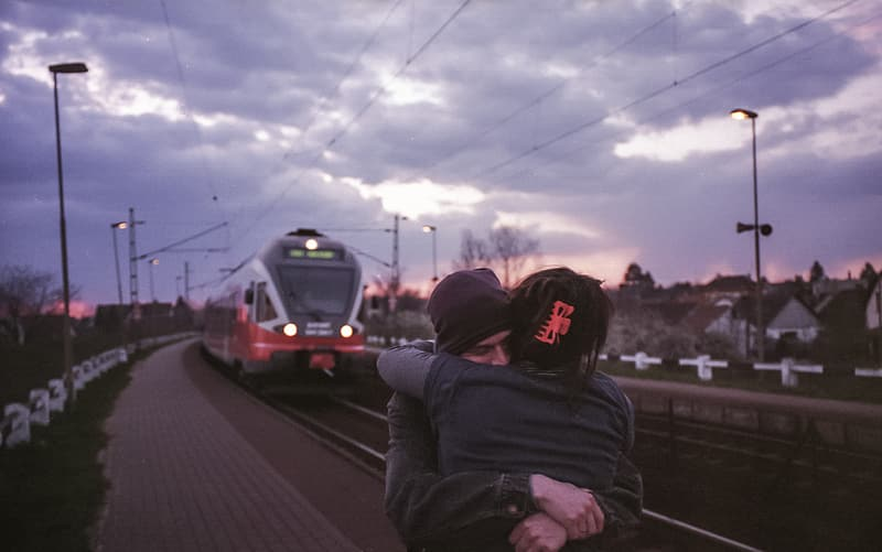Two persons hugging each other on train station platform
