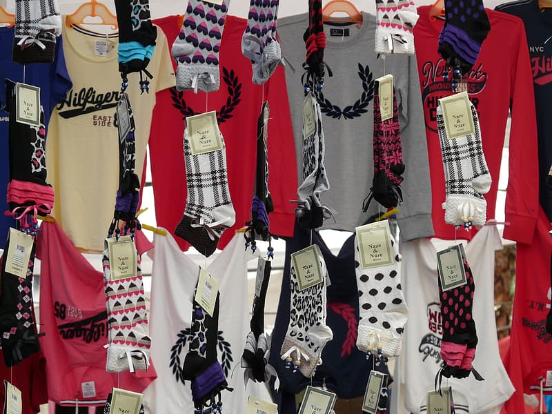 Assorted-color shirts and socks hang near wall
