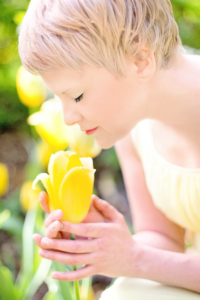 Woman smelling yellow tulip flower