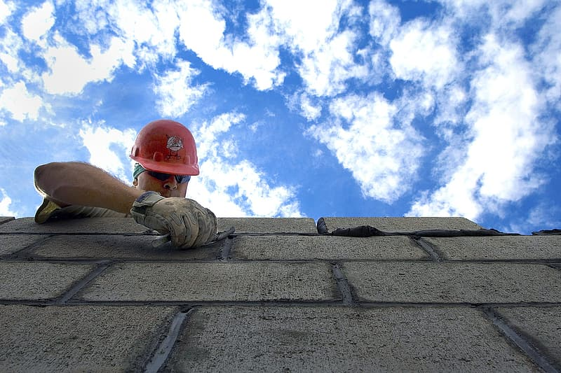 Man in red hard hat on top of cinder block