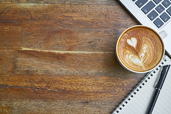 Cappuccino beside lined paper with pen