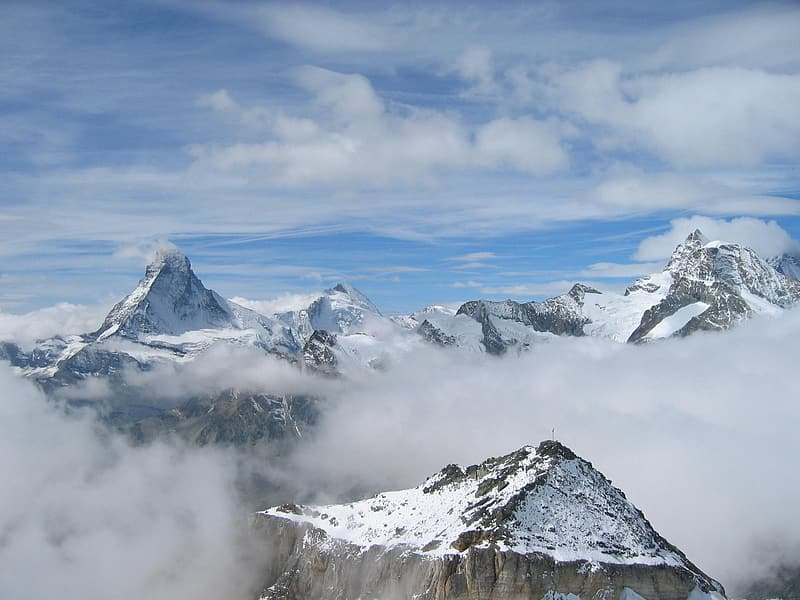Photography of mountains coated with snow under blue and white cloudy sky