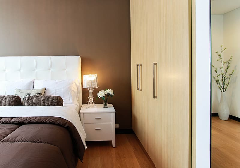 Brown wooden wardrobe near white wooden nightstand with lighted table lamp