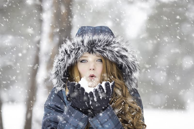 Woman in coat blowing snows