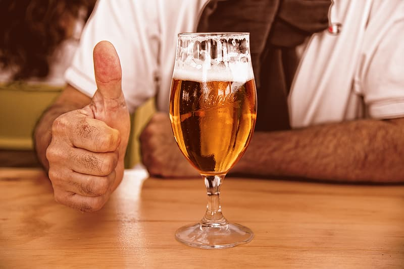 Person gesturing thumbs up beside almost-filled cocktail glass