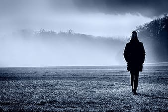 Grayscale photo of woman in black coat standing on grass field