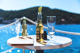 Beer and lager bottles and glasses on a table on the coast in summer time