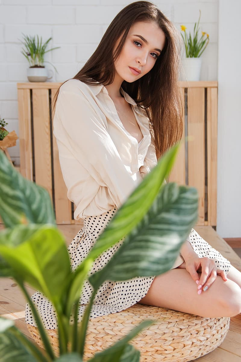 Woman wearing blouse and skirt sitting on ottoman near plant
