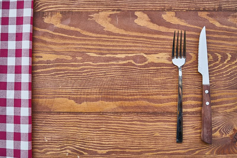 Stainless steel fork and knife on brown wooden surface