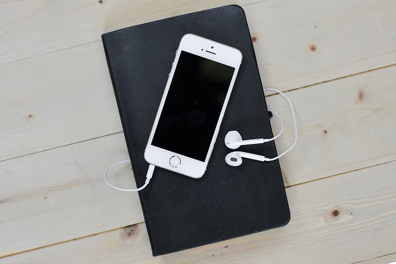Silver iPhone 5s with EarPods on top of black notebook