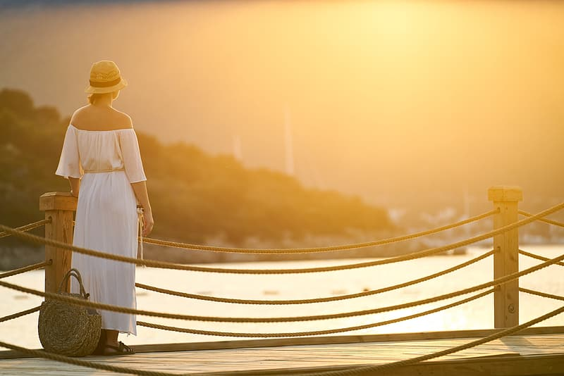 Woman in white dress standing on white wooden bridge during daytime