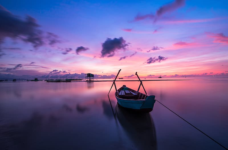 Canoe on body of water with blue and pink sky