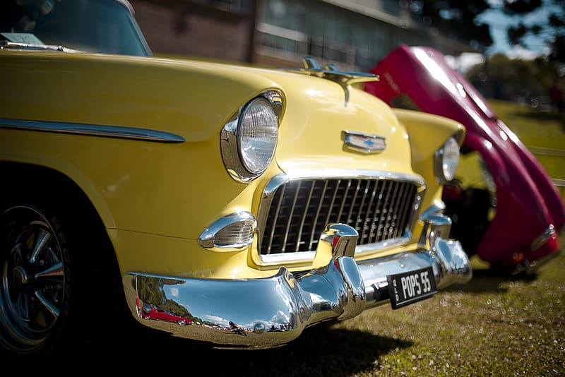 Classic yellow Chevrolet parked beside red car