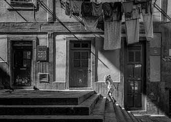 Gray scale photo of girl on stairs under assorted hanged clothes