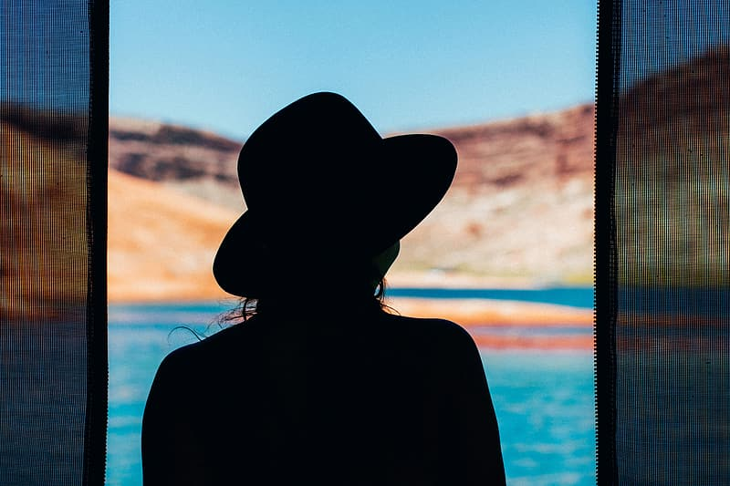Woman wearing black hat standing near body of water during daytime