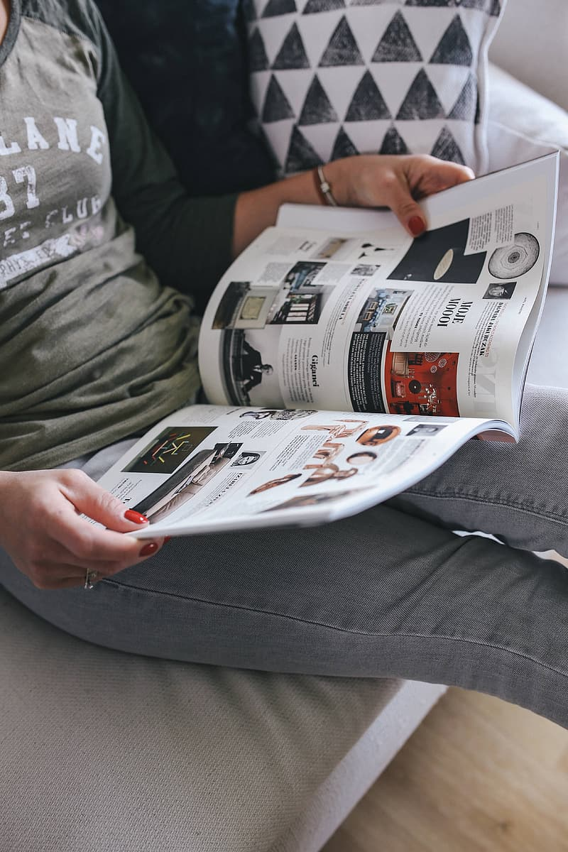 Person in gray pants reading newspaper
