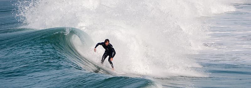 Man riding surfboard at the ocean during day