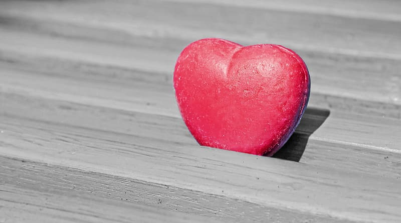Heart-shaped ornament on brown wooden surface