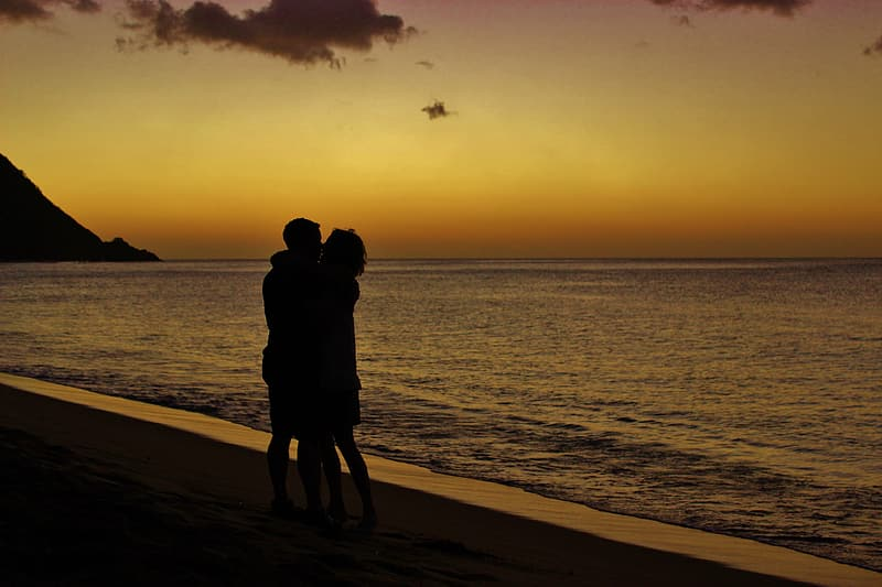 Silhouette of couple kissing on beach during sunset