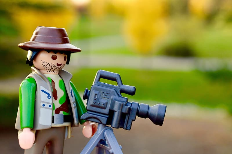 Selective focus photography of toy camera man with camera